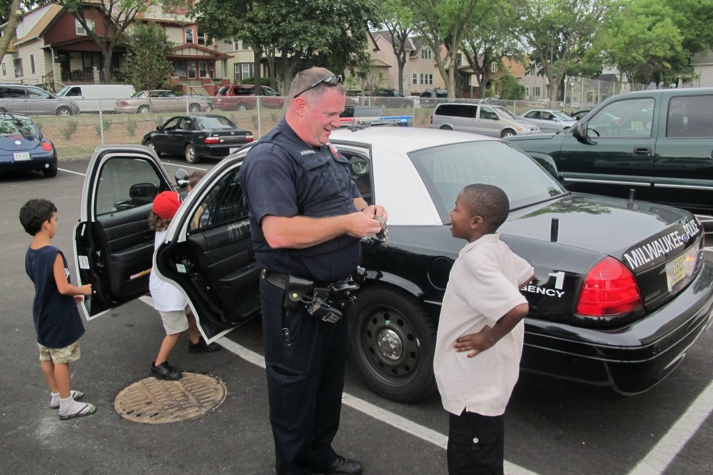 A Milwaukee police officer talks with a boy in Clarke Square. (Photo by Edgar Mendez)
