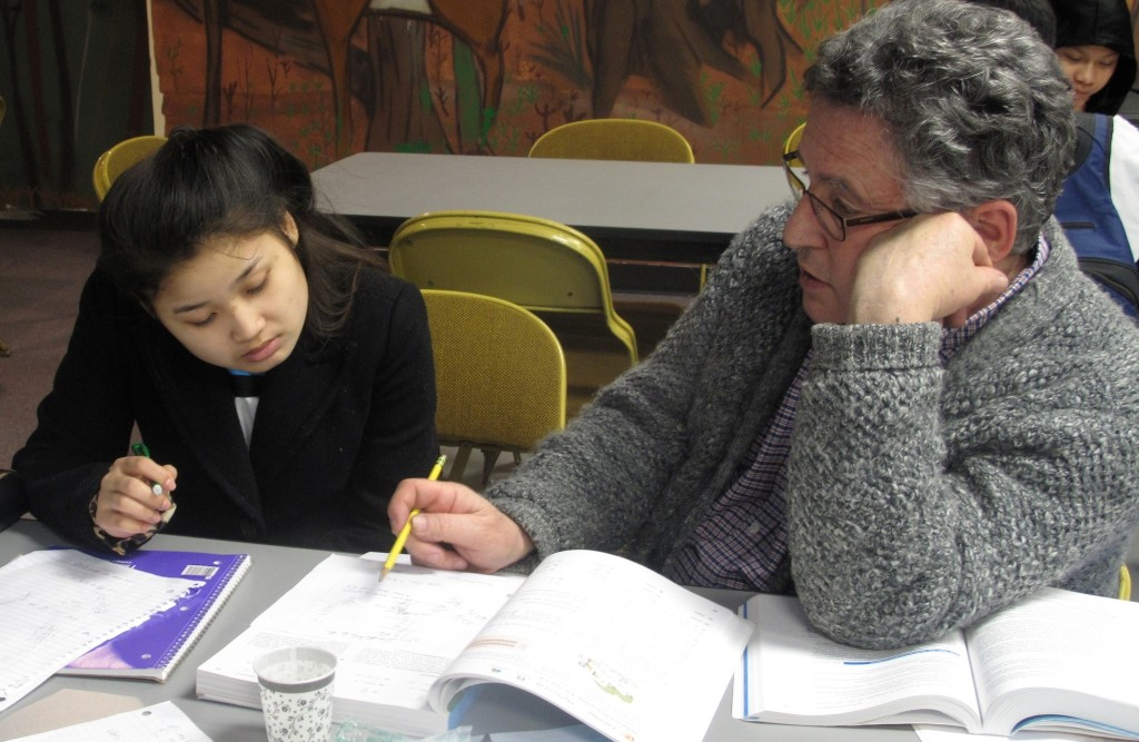 Robert Heffernan (right), Burmese Immersion Project co-founder, helps student Naw Paw Say Wah with her math homework. (Photo by Teran Powell)