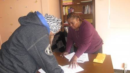Outreach worker Shavon Pope helps a program participant update her personal information. (Photo by Andrea Waxman)