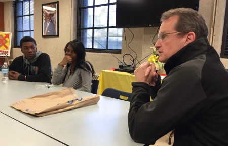 Jim Bohn (right) shares his experiences as a former undercover investigator for the Drug Enforcement Agency with youth in Harambee. (Photo by Wyatt Massey)