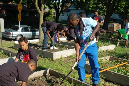 Trevis Hardman (in white T-shirt), 22, who grew up across the street from the garden at 9th and Ring streets, works with the boys. (Photo by Andrea Waxman)