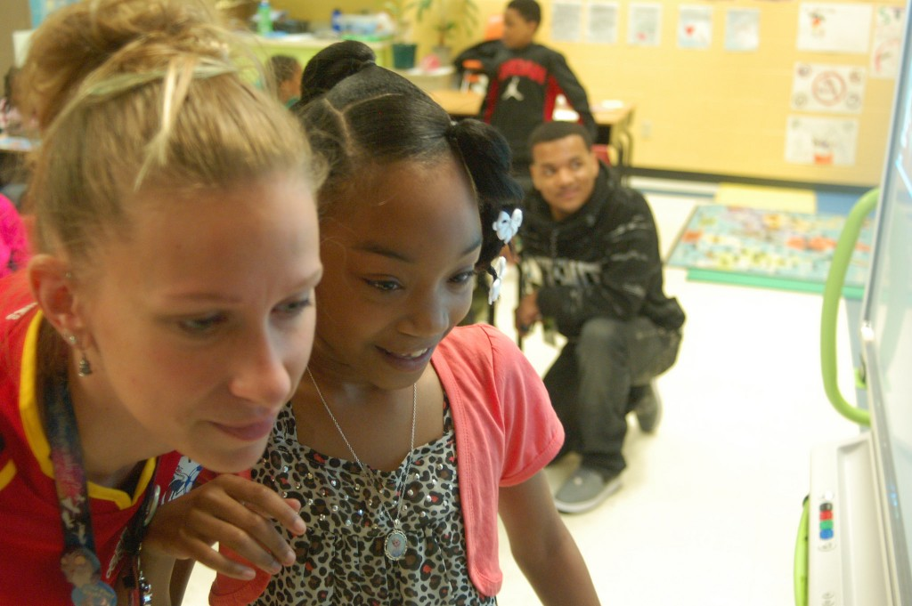 Mia Hunt, 8, is excited to see the Ugandan students' faces on Skype as Laura Kolar looks on. (Photo by Andrea Waxman)