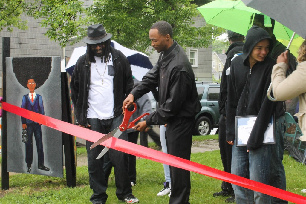 Antoine Carter (left) watches as County Supervisor Martin Weddle (right) cuts the ribbon at the official unveiling painting by ArtWorks interns at the Rays of Sunshine garden. (Photo by Madeline Kennedy)