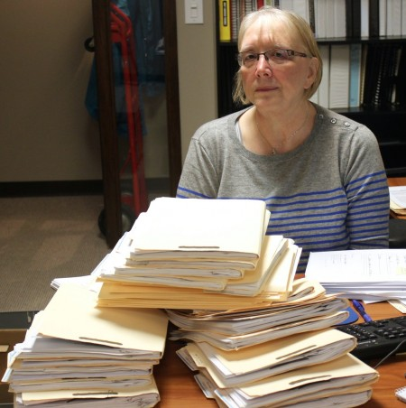Dorothy Dean, a volunteer at Metropolitan Milwaukee Fair Housing Council, follows up on stacks of mortgage rescue scam cases. (Photo by Matthew Wisla)