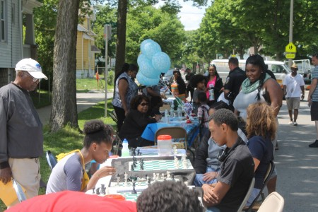 Amani residents play chess at a block party on Chambers between 23rd and 24th streets. (Photo by Madeline Kennedy)