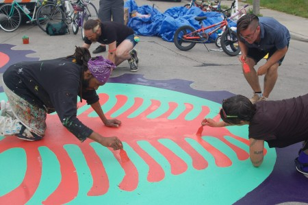Artists Ammar Nsoroma, Angie Livermore and community members painted all day to complete the mural in time. (Photo by Devi Shastri)
