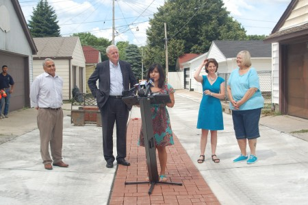 Iris Gonzalez of Sixteenth Street Community Health Centers explains the impact of the green alley as Public Works Commissioner Ghassan Korban, Mayor Tom Barrett, Vicky Elkin and resident Kathie Mervyn look on. (Photo by Devi Shastri)