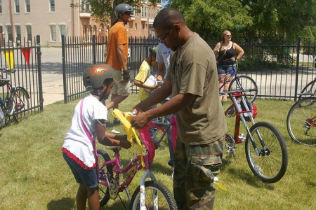 Christ Washington helps his daughter Shalisa decorate her bike. (Photo by Allison Dikanovic)