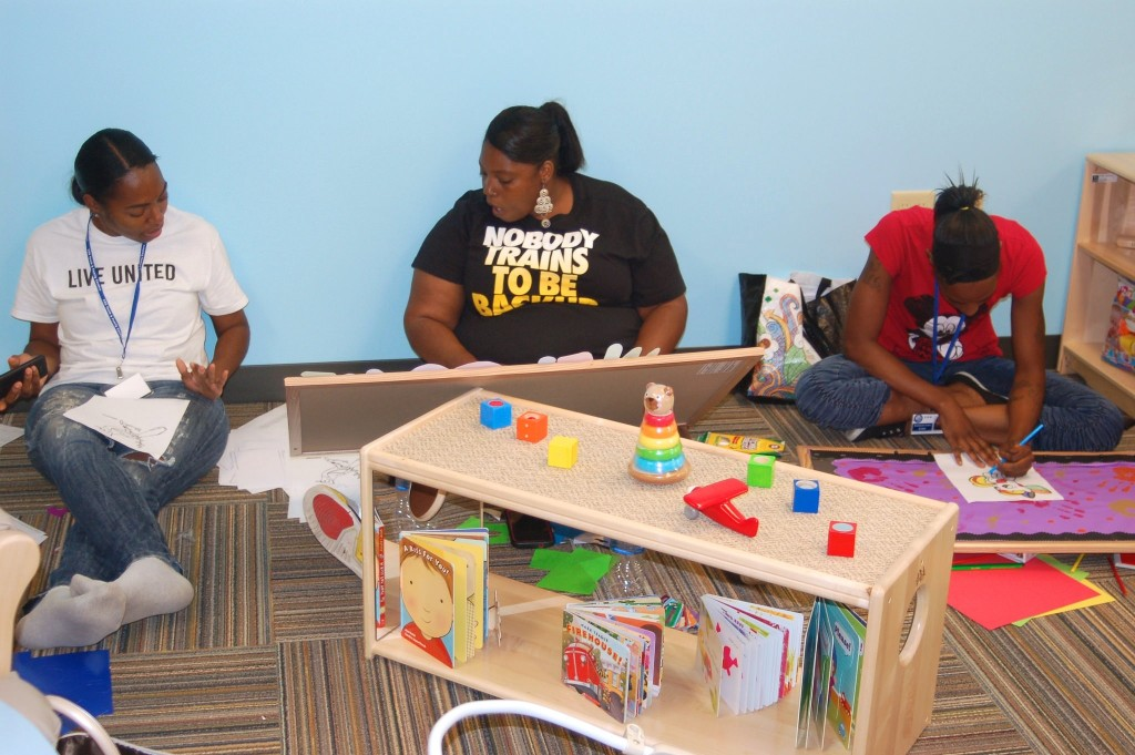 Burke Center teachers (from left): Lashaunda Payton, LaDonna Walton and Madelyn Evans prepare bulletin boards for the new classrooms. (Photo by Andrea Waxman)