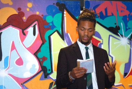 """Domonique Whitehurst reads his original poem about lessons Tracy Rolkosky is learning from the challenges of poverty for """"My Sister's Story."""" (Photo by Andrea Waxman)"""