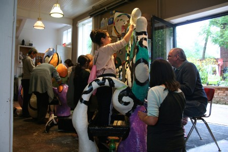 """Volunteers paint a sculpture named """"Water Heart"""" that will be installed in Pulaski Park. (Photo by Jabril Faraj)"""