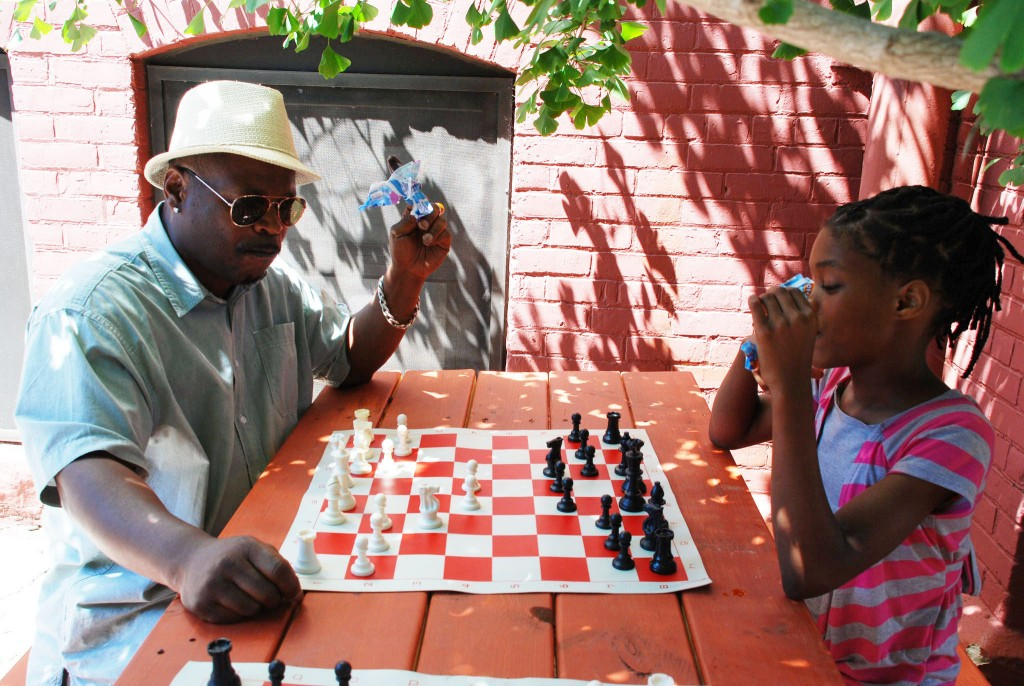 Quan Caston and student Kathy Ford share a game of chess and popsicles at Auer Avenue School. (Photo by Andrea Waxman)