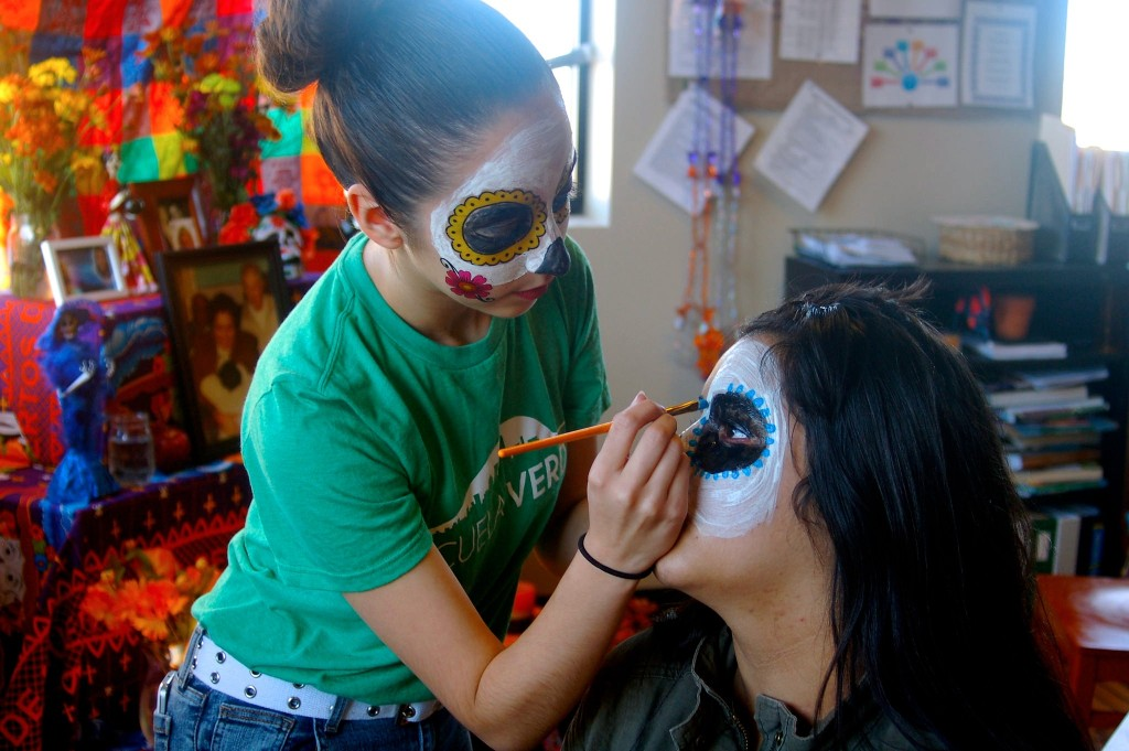 Isabel Castro paints her friend Diana Diaz's face in the traditional style of the calavera before their Dia de los Muertos celebration at Escuela Verde. (Photo by Allison Dikanovic)