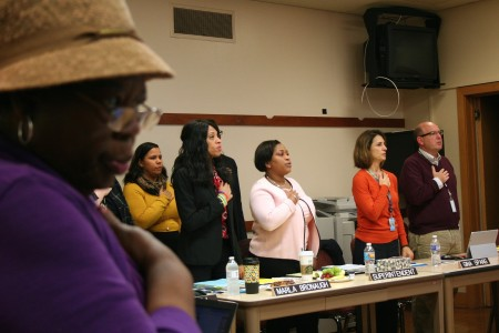 Director Annie Woodward (left foreground) and MPS administrators recite the pledge of allegiance before a retreat focused on charter schools. (Photo by Jabril Faraj)