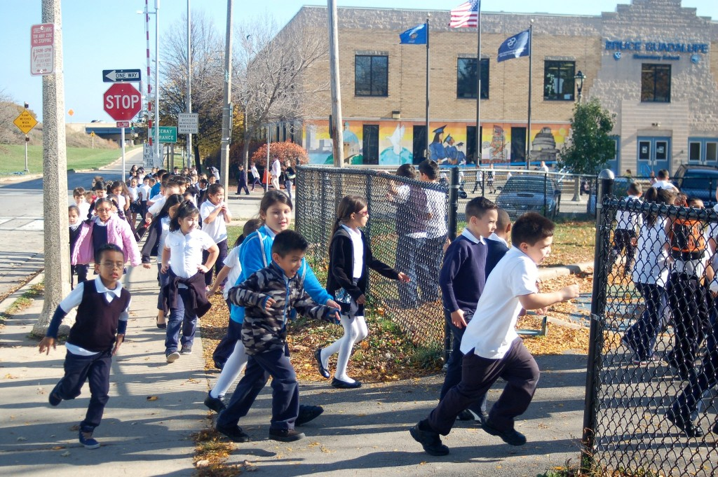 Bruce Guadalupe Community School students rush to the playground in Walker Square Park during recess. (Photo by Edgar Mendez)