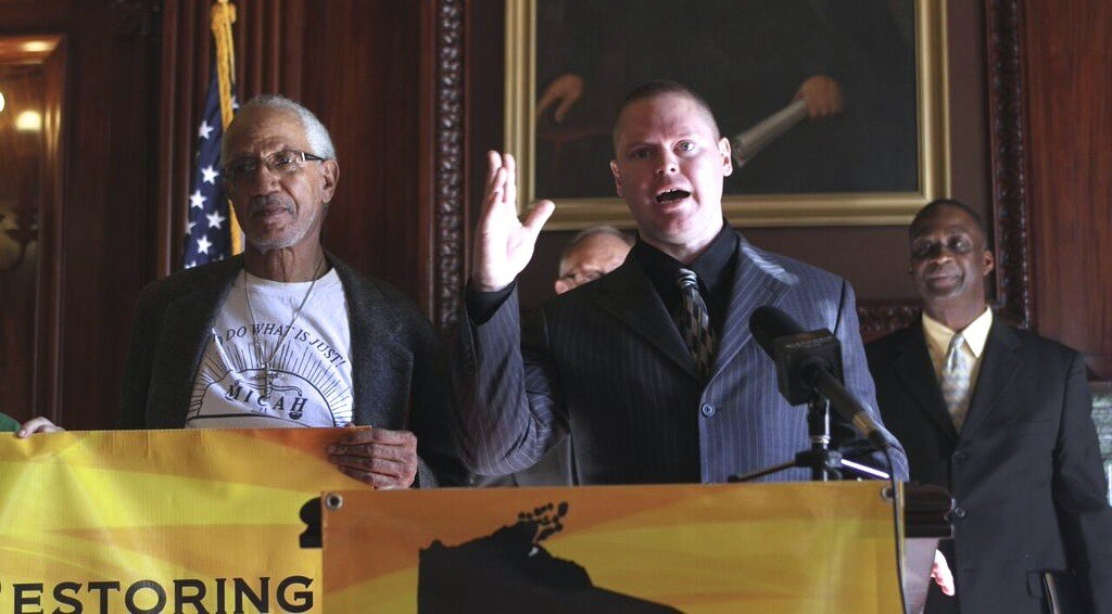 Mark Rice (at microphone) speaks at a press conference at the State Capitol to launch the ROC Wisconsin campaign on Nov. 3. He is joined by EXPO leaders Jerome Dillard (left) and William Harrell (background).