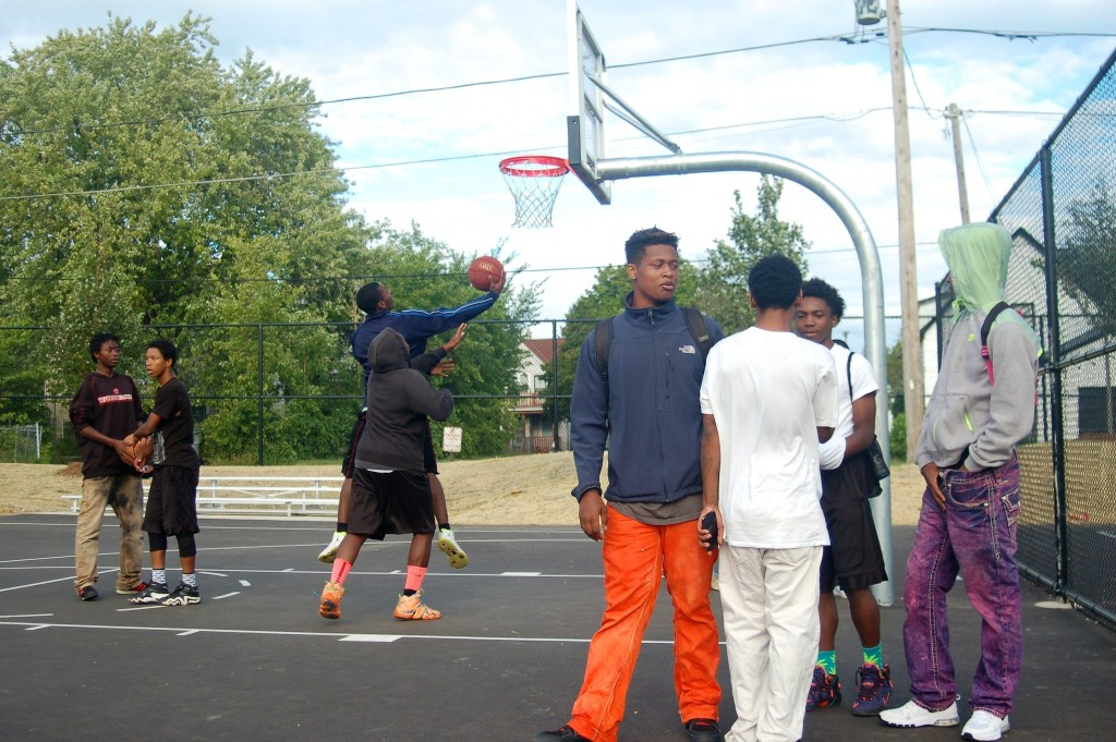 Young men wait their turn to play basketball during the opening day celebration at Moody Park. (Photo by Edgar Mendez)