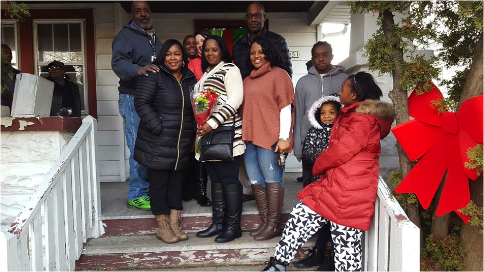 The Burkes family with ACTS Housing team members posing in front of her new home. (Photo courtesy of ACTS Housing)