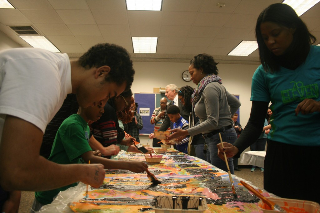 Milagro Jones (front left), Mayor Barrett (back) and others paint one of two canvases for the King Library's community mural on MLK Day. (Photo by Jabril Faraj)