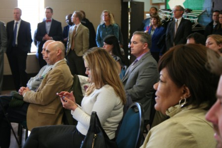 A crowd of corporate partners and local government employees looks on during the announcement. (Photo by Jabril Faraj)