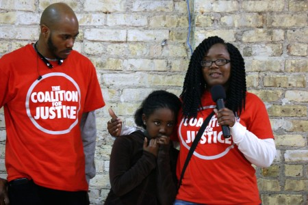 Markasa Chambers (left) and Nate Hamilton, co-founder of the Coalition for Justice, comfort Zoe Chambers, 8, as she tries to speak to the group. (Photo by Jimmy Gutierrez)