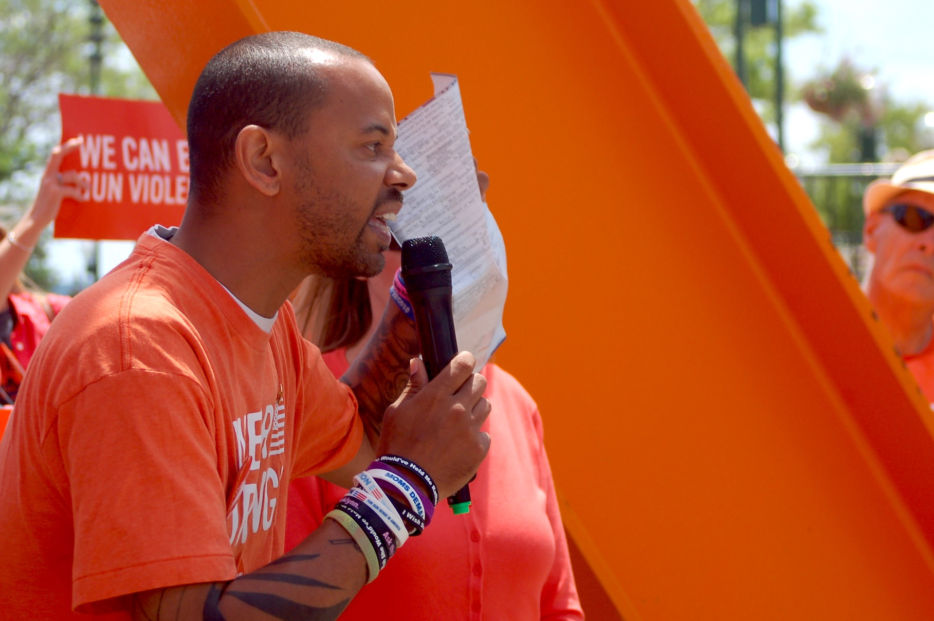 Khary Penebaker, a candidate for U.S. Congress, holds his mother's death certificate as he tells a crowd at a gun violence awareness rally about her suicide in 1979. (Photo by Brendan O'Brien)