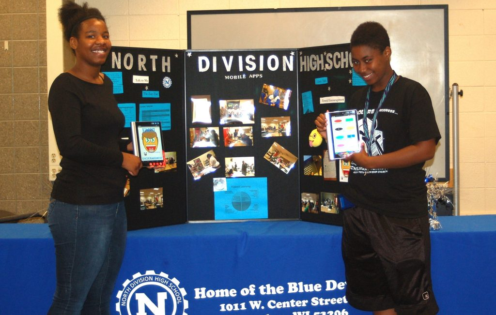Tatiana Loyd and Qiaira Mathews pose with their app displayed on tablets. (Photo by Rebecca Carballo)