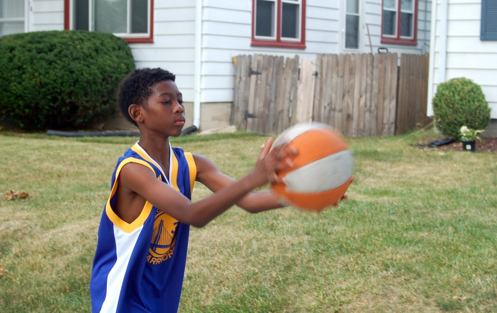 J'Ali Thornton practices with a basketball in front of his house. (Photo by Andrea Waxman)