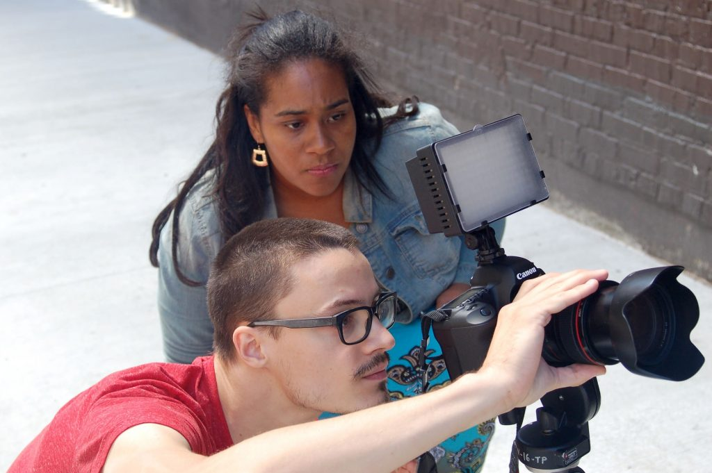 Tyshun Wardlaw directs videographer Mitchell Mittelstedt as he films a muralist working in Black Cat Alley, on the East Side. (Photo by Andrea Waxman)