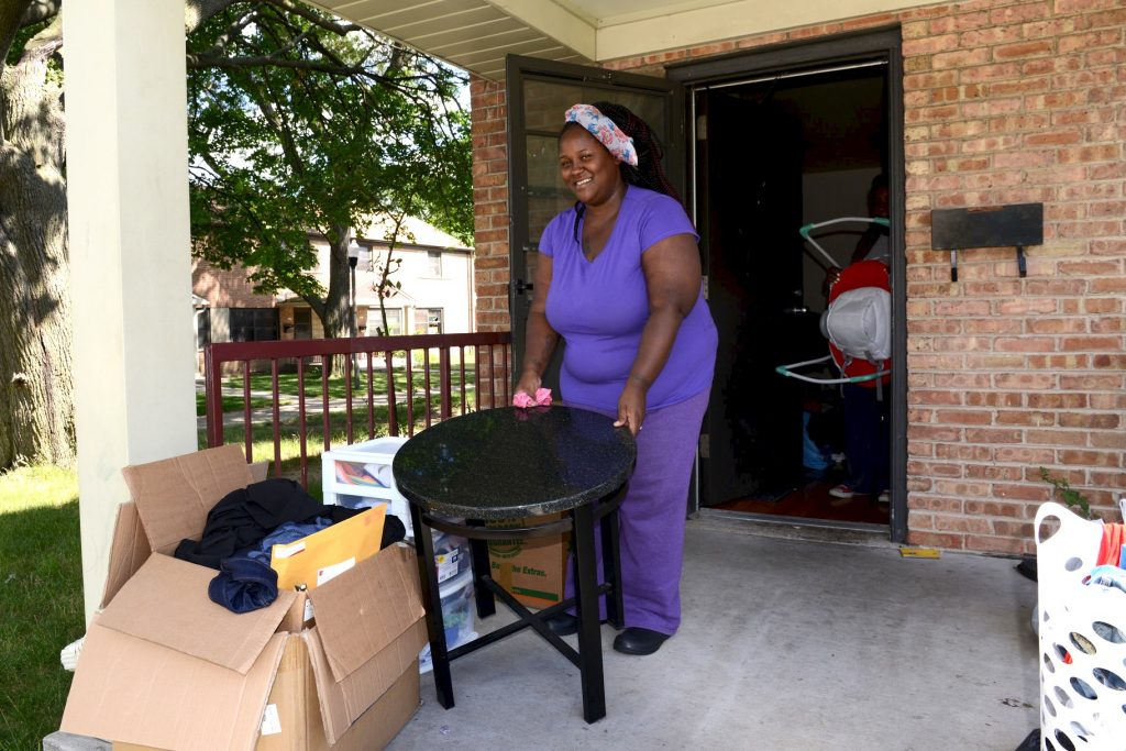 Mateka Young carries a table out of her apartment at 6701 W. Silver Spring Drive. Young was among the first residents to move out of the western section of Westlawn. (Photo by Sue Vliet)
