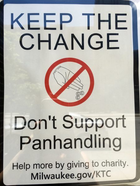 Local businesses hang signs in their windows to deter panhandling. (Photo By Rebecca Carballo)