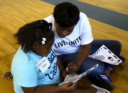 Rockwell intern Marquita Smith, 32, helps a student choose words for a writing activity at the literacy fair. (Photo by Amelia Jones)