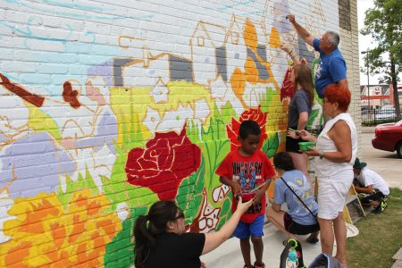 South Side residents work to complete mural on supermarket wall