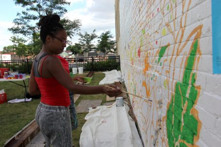 Artist Tia Richardson works on the mural. (Photo by Rebecca Carballo)