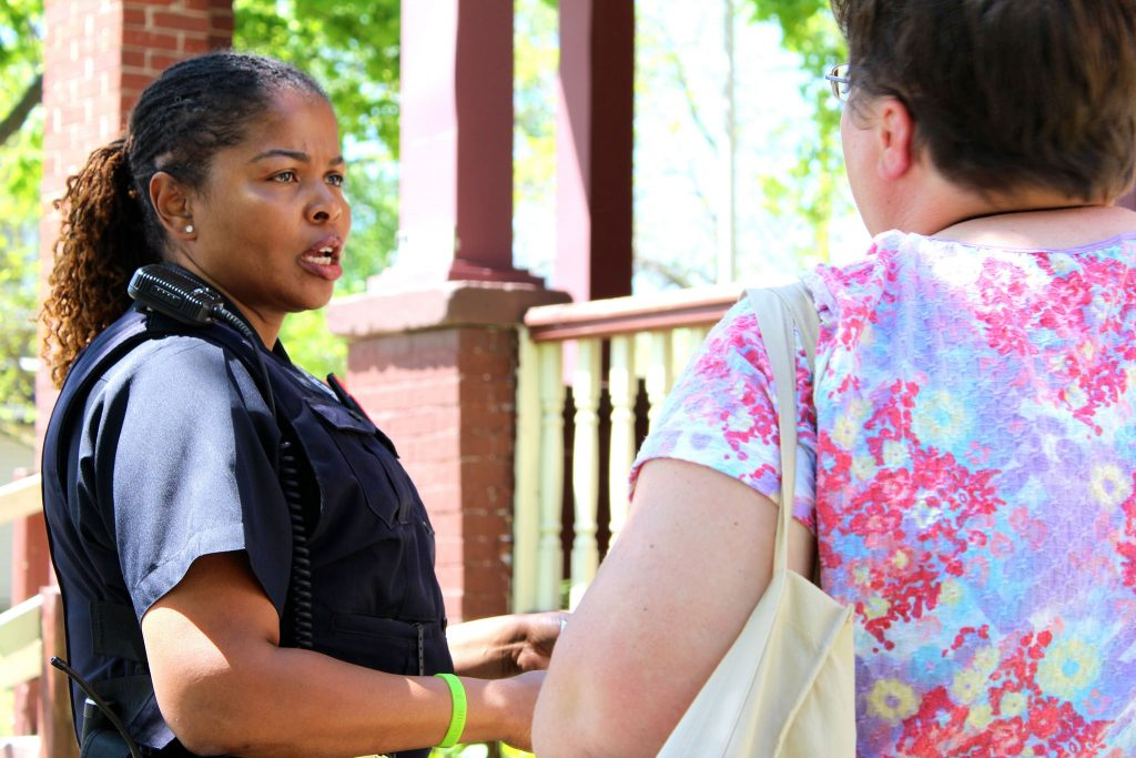 Milwaukee Police Department Community Liaison Officer Melissa Jones talks to a community organizer in the Midtown neighborhood. (Photo by Mark Doremus)