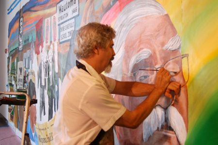 Raoul Deal, lead artist and senior lecturer at UW-Milwaukee's Department of Art and Design at the Peck School of the Arts, touches up an image of Jesus Salas. (Photo by Edgar Mendez)