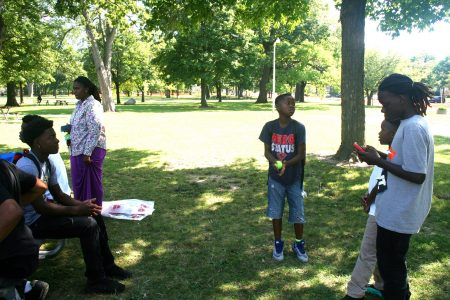Young people, including Niekale Steward (seated), hang out at Sherman Park. (Photo by Jabril Faraj)