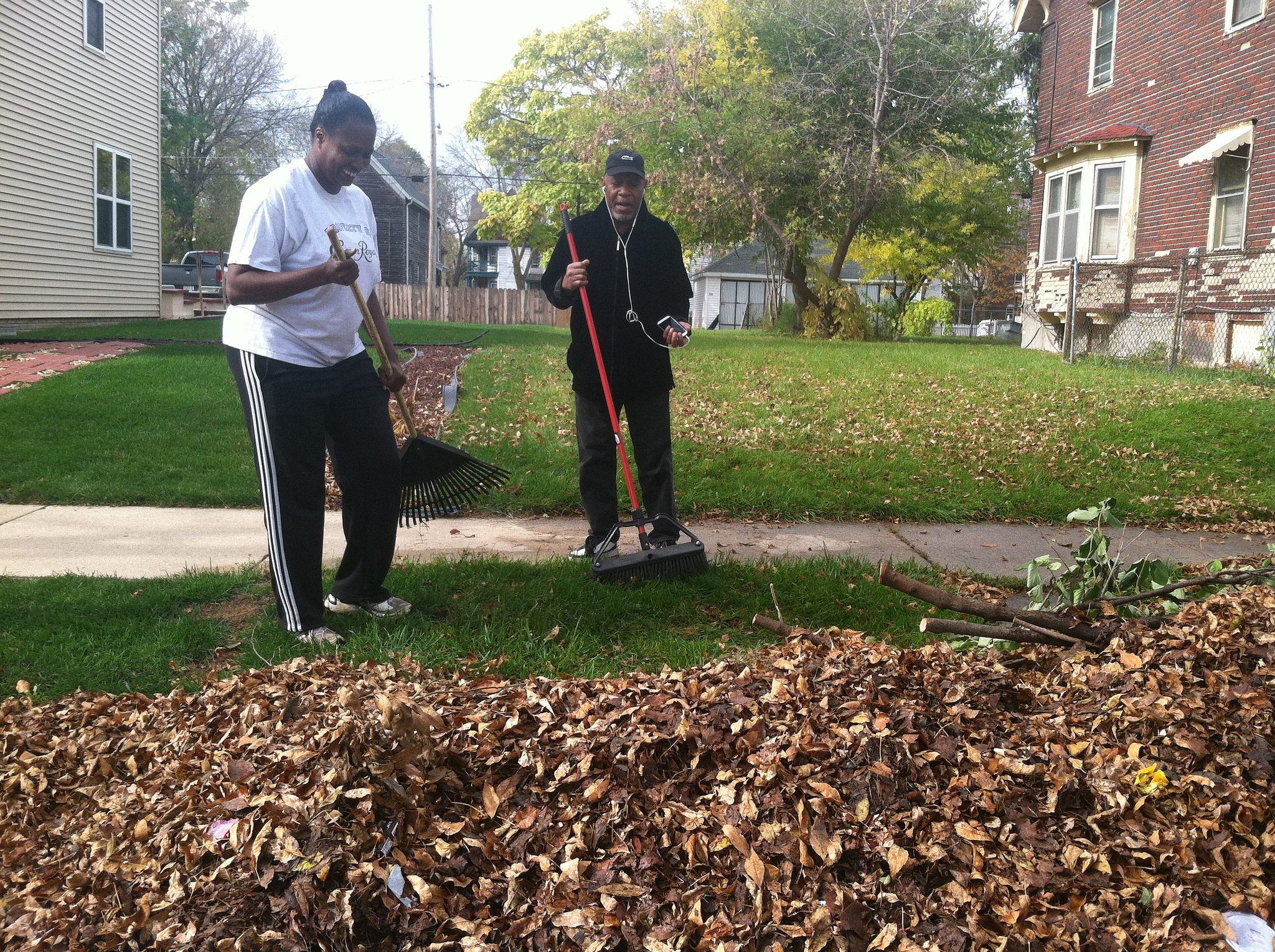 Gladys Carroll-Weathersby, resident, and Jack Hill, son of a resident, raking leaves on the 2400 block of N. 16th Street