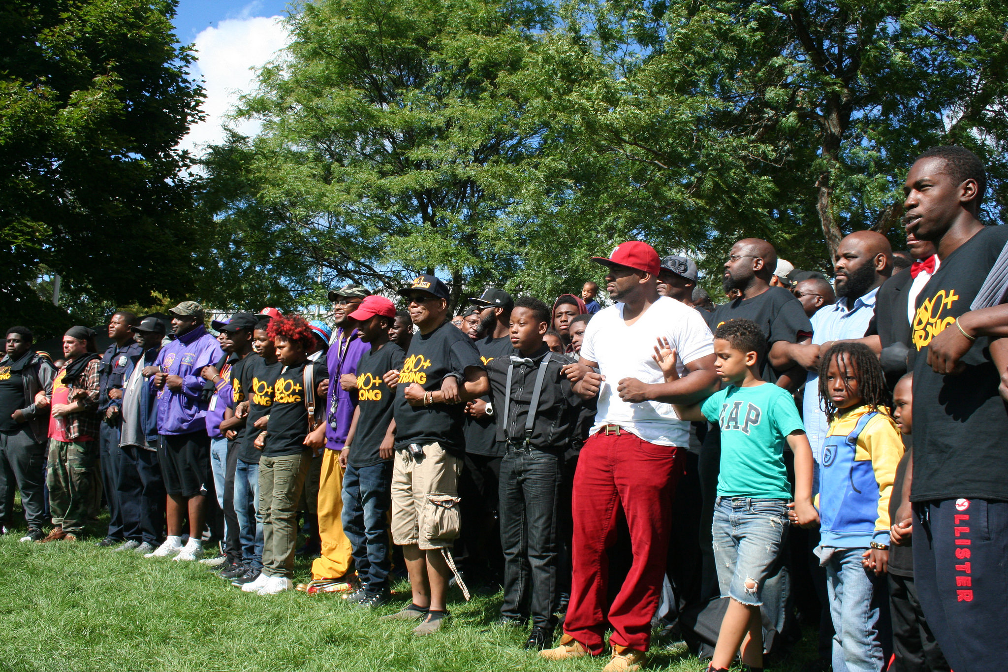Black men and boys lock arms at the event. (Photo by Jabril Faraj)