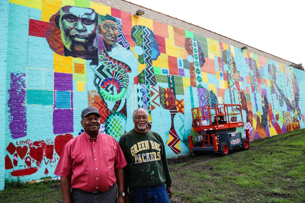 Wisconsin Black Historical Society founder and director Clayborn Benson (left) and artist George Gist stand in front of the nearly completed mural. (Photo by Allison Steines)