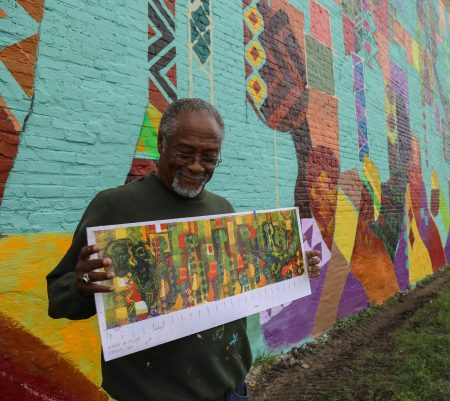 George Gist holds up his original drawing for the mural, which spans 125 by 50 feet, making it the largest mural he has ever done. (Photo by Allison Steines)