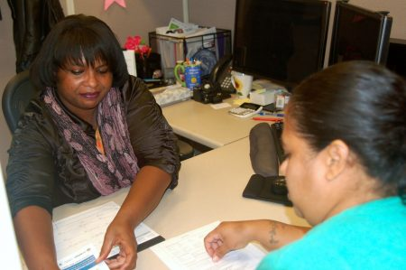 Vanessa Burkett provides Lizbeth Estrada with information about the energy assistance program. (Photo by Brittany Carloni)