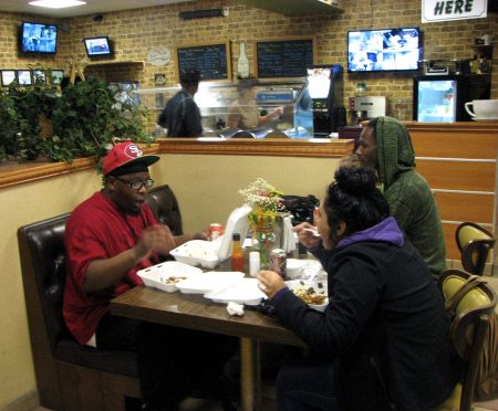 Shannon Reyes (left), Andre Moore and Abigail Velazquez eat dinner at Daddy's Soul Food and Grille. (Photo by Clara Hatcher)