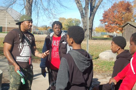 Vaun Mayes (left) talks to several teens riding bikes in the neighborhood about joining the Sherman Park Youth Stipend Program. Volunteer mentor Derrick Madlock (second from left) looks on. (Photo by Andrea Waxman)