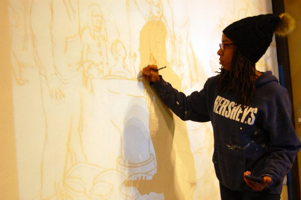 Tia Richardson traces the outline of a mural she is working on at All People's Church. (Photo by Brittany Carloni)