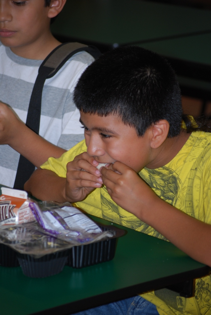 A youth enjoys a lunch prepared by SDC's Food Service Program as part of the 2012 Summer Food Service Program.