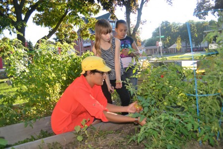 Jezamil Vega-Skeels (left) shows kids tomato plants at a community garden near a mobile bike hub site. (Photo by Tom Momberg)