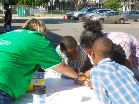 A volunteer helps Denischa Harvester and her family register for the Big Day of Serving. (Photo by Maria Corpus)