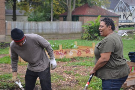 Danell Cross (right) talks to a young resident hired to work on the raingarden. (Photo by Tom Momberg)