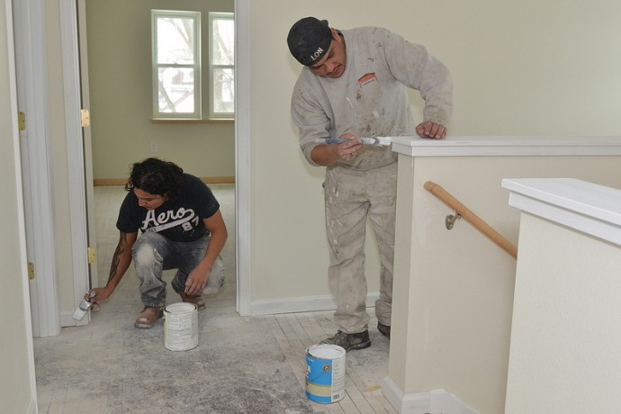 Ricardo Avila and Rodolfo Garcia add a fresh coat of paint to the interior of the renovated home on South 33rd Street. (Photo by Sue Vliet)
